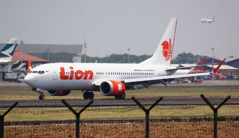 A passenger jet emblazoned with Lion Air logos taxis down a runway.