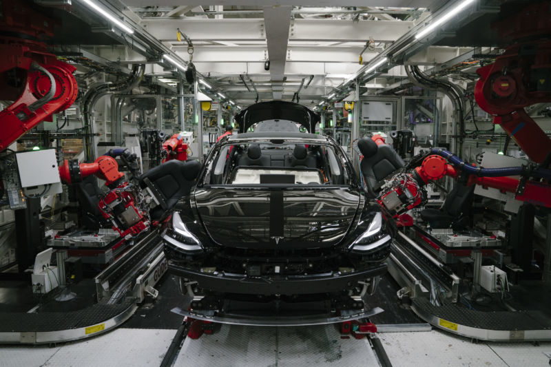 Robotics arms install the front seats to a Model 3 at the Tesla factory in Fremont, California.