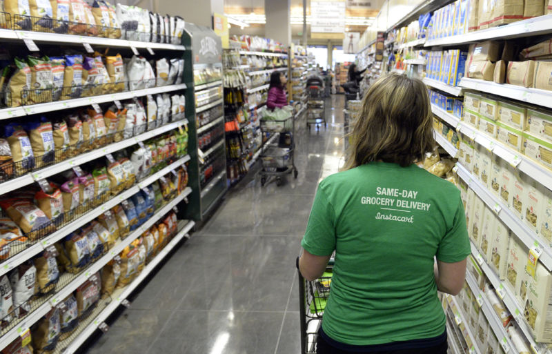 Kaitlin Myers, a shopper for Instacart, navigates the aisles as she shops for a customer at Whole Foods in Denver. Myers receives a grocery list from an Instacart customer and then completes the shopping on Tuesday, October 28, 2014.