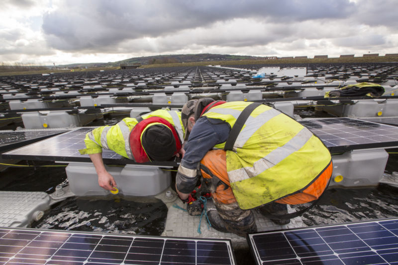 Two people working on a floating solar installation