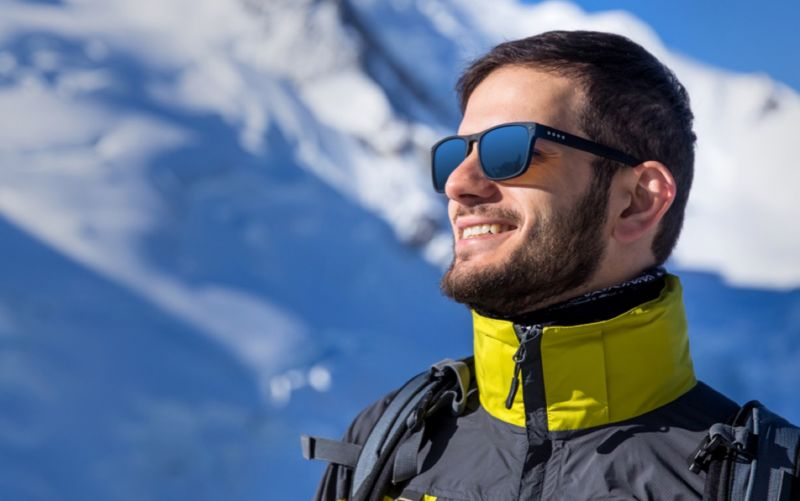 Dude enjoying winter sports in sunglasses is happy.