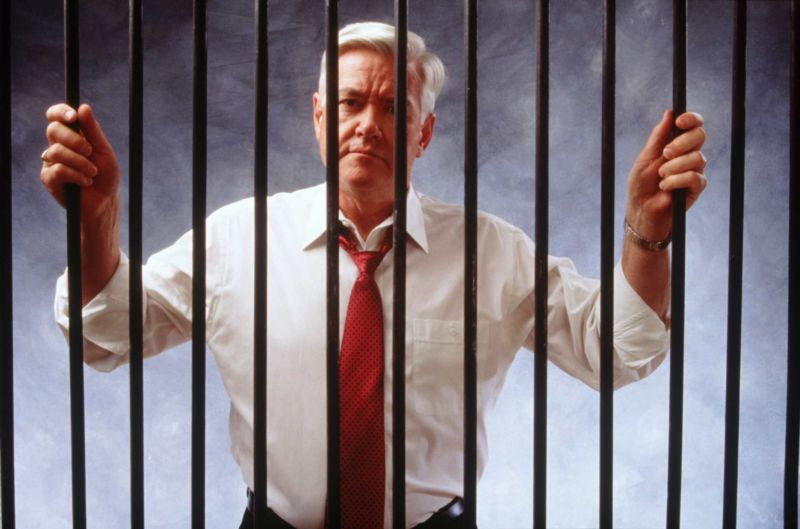 A man with white hair, wearing a button-down shirt and tie, standing behind the bars of a jail cell.