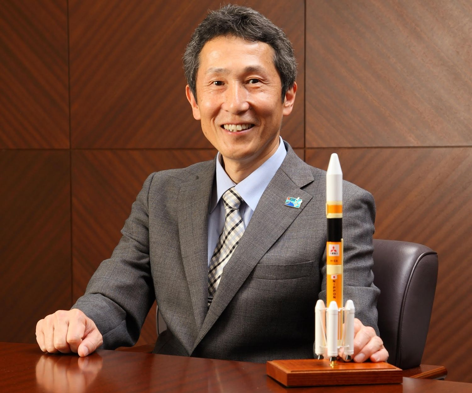 Ko Ogasawara, vice president & general manager of Space Systems at Mitsubishi Heavy Industries, poses with a model of an H-2A rocket.