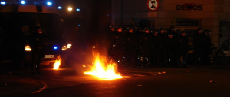 Image of a fire burning in front of riot police.