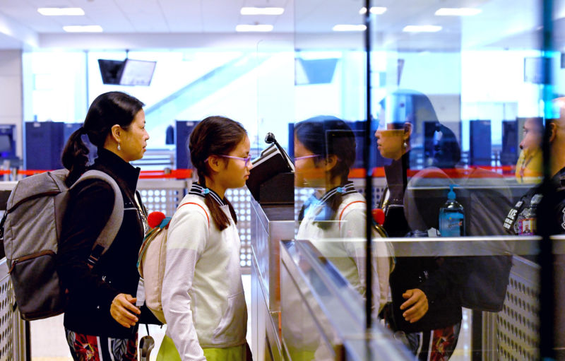 After arriving from China, Wenhong Chen and Funina Wu, from Frederick, Maryland, are photographed at Dulles as part of the US Customs and Border Protection's newly implemented biometrics system.