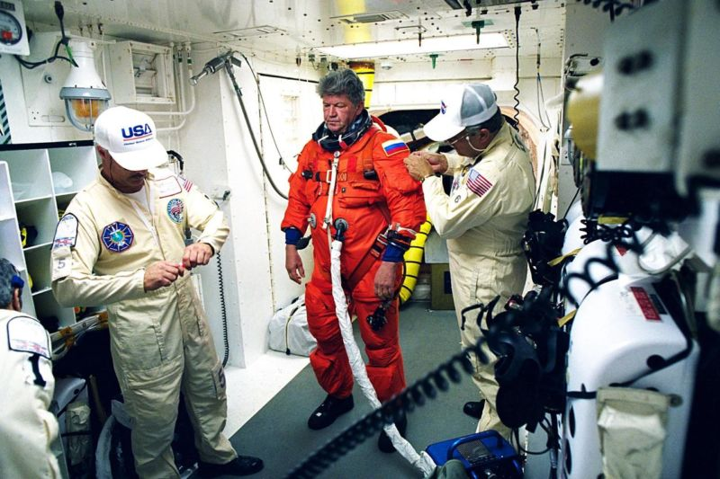 In 1998, STS-91 Mission Specialist and Russian cosmonaut Valery Victorovitch Ryumin is assisted with his flight suit prior to his entry into the space shuttle <em>Discovery</em>.&#8221;></p> <p style=