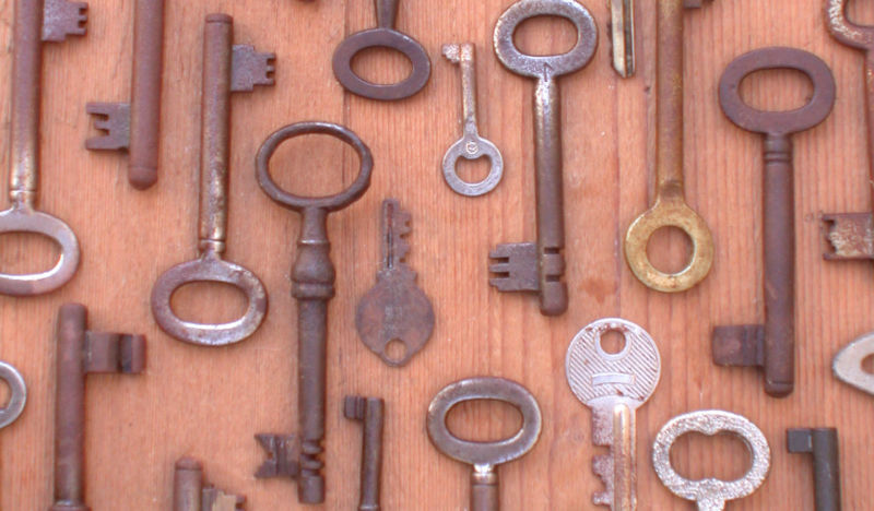 A large number of keys against a light-colored wooden background.