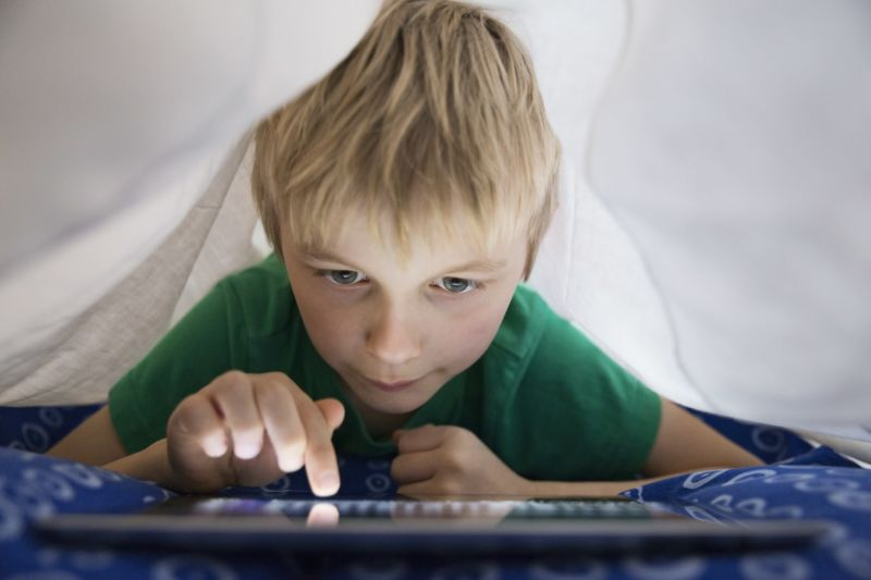 A boy tapping the screen of a tablet computer.