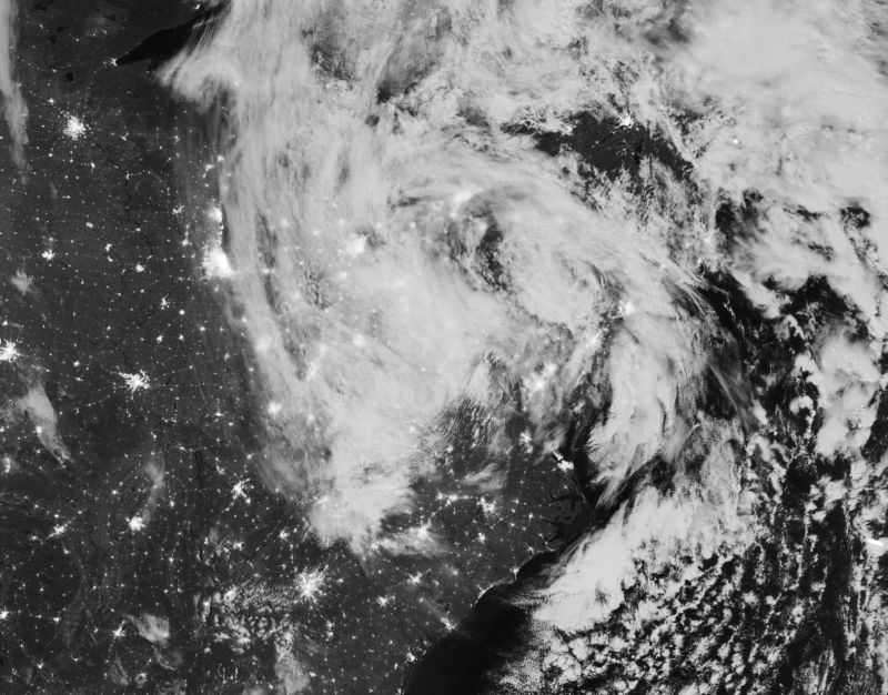 Black-and-white satellite photograph of storm clouds over land and ocean.
