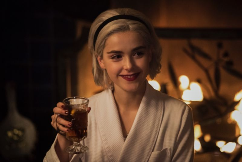 "Sabrina Spellman (Kiernan Shipka) toasts friends and family at the witchy winter solstice in <em>The Chilling Adventures of Sabrina</em> holiday special.""></p> <p style="