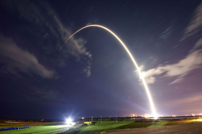 An early-morning rocket launch traces an arc of light across the horizon.
