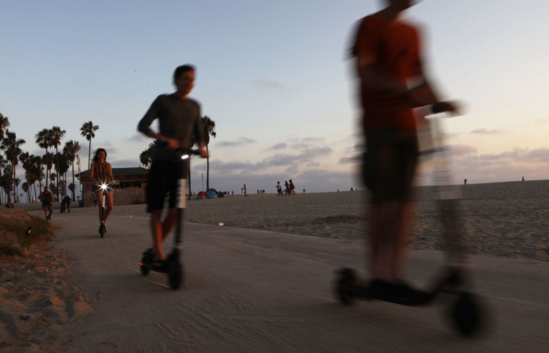 People ride shared dockless electric scooters along Venice Beach on August 13, 2018 in Los Angeles, California.