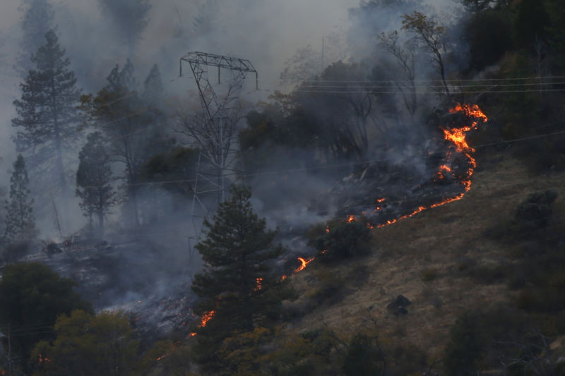 PG&E transmission tower surrounded by fire.
