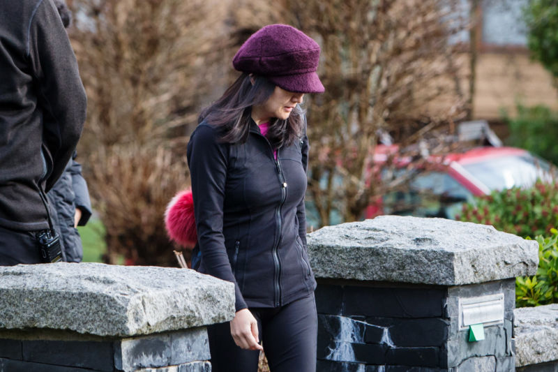 A woman walks toward a sidewalk while a hat obscures part of her face.