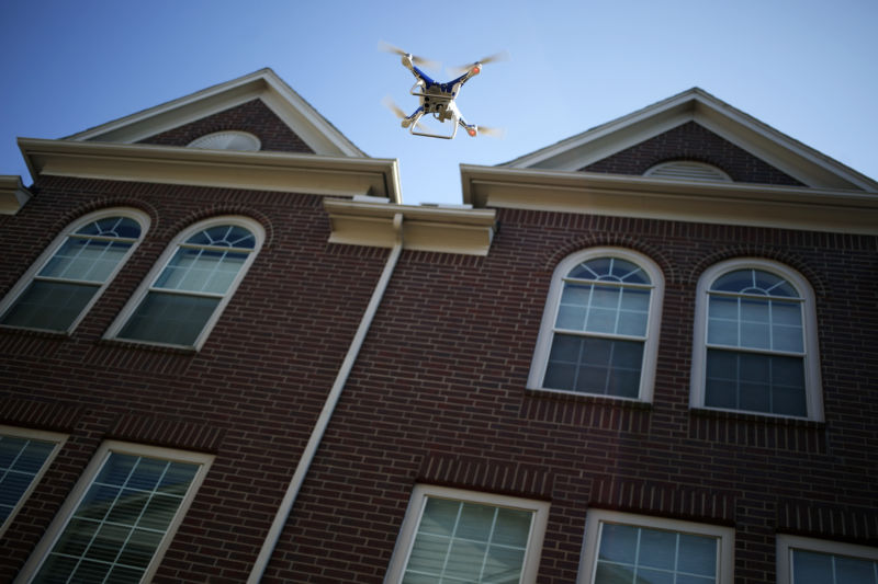 Unmanned aircraft being flown over large house.