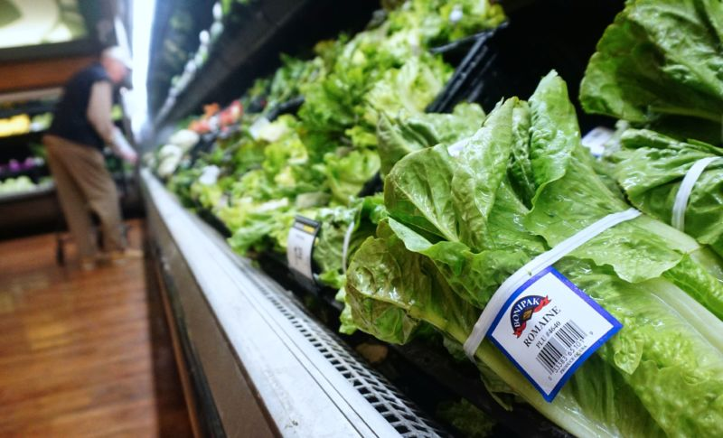 A man shops for vegetables beside Romaine lettuce stocked and for sale at a supermarket in Los Angeles, California, on May 2, 2018, where the first death from an E coli contaminated Romaine lettuce outbreak was reported.
