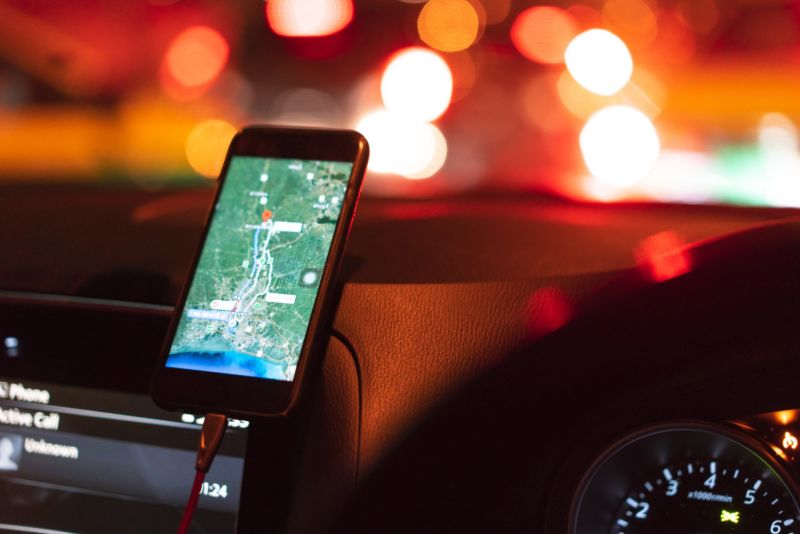 A smartphone displaying a map while propped up on a car dashboard.