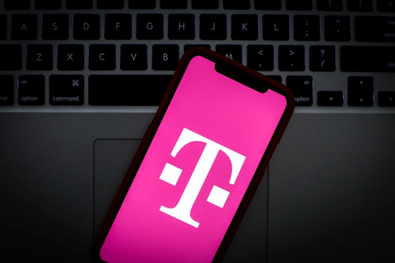 T-Mobile's logo on the screen of a smartphone that's laying on top of a laptop keyboard.