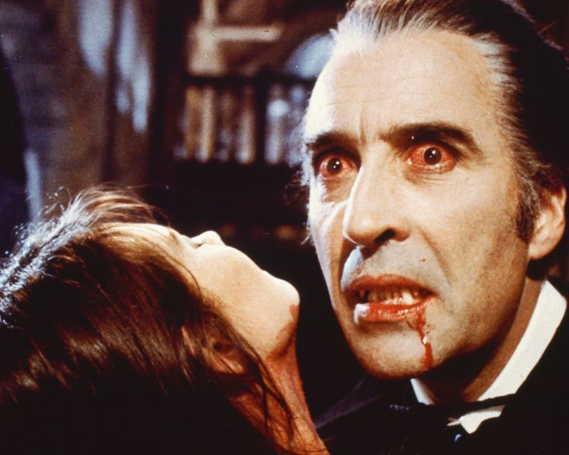 Still image from a Hammer horror film in which a vampire (Christopher Lee) sucks blood from an attractive female victim.