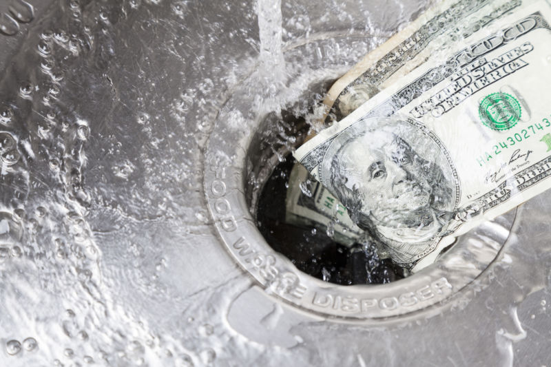 Money being washed down a garbage disposal.