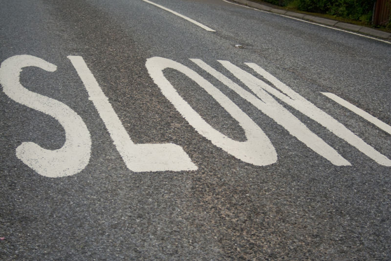 The word SLOW has been painted on a street for the benefit of drivers.