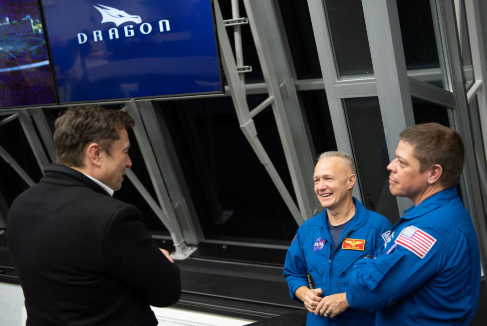 SpaceX founder Elon Musk shares a laugh with NASA astronauts Doug Hurley, center, and Bob Behnken, in the launch control room at Kennedy Space Center Friday night.