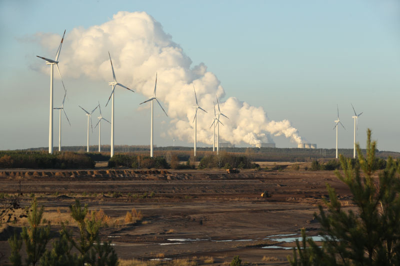 Wind turbines near a coal plant.