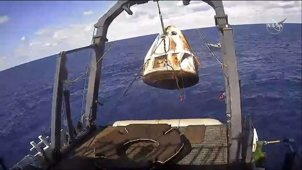 The Go Searcher recovery vessel brings Dragon on board.
