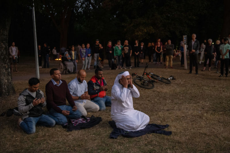 People look on as men pray in a park near Al Noor mosque after a terrorist killed 50 people.
