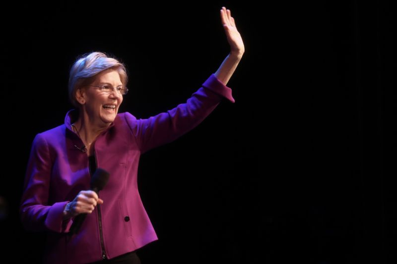 Elizabeth Warren holding a microphone and waving while speaking to a crowd.