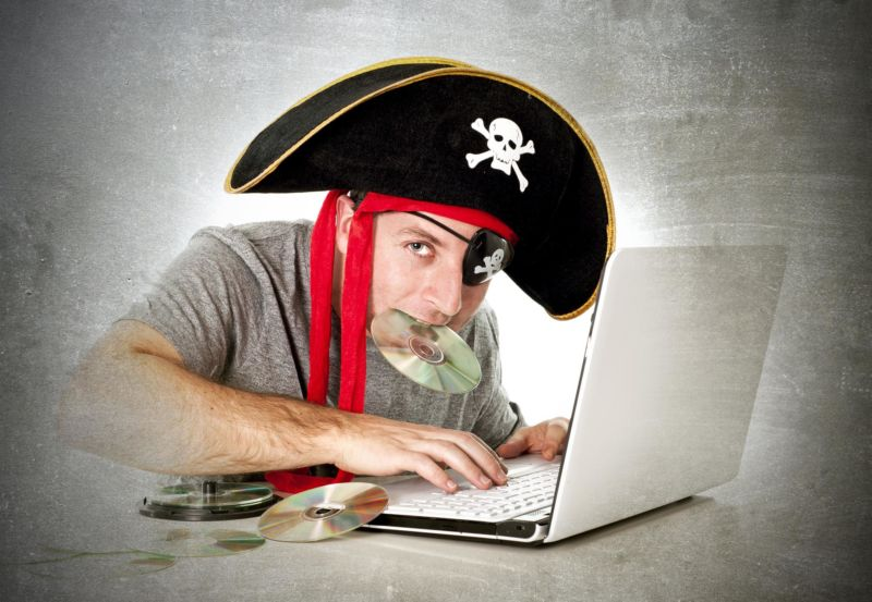 A man, surrounded by music CDs, uses a laptop while wearing a skull-and-crossbones pirate hat and holding one of the CDs in his mouth.