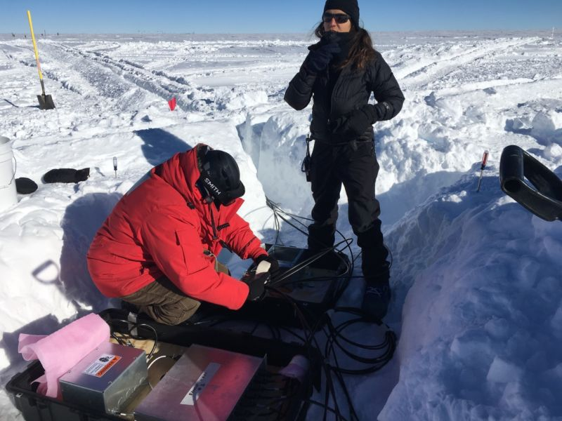 Image of people working on electronics in a snow trench.