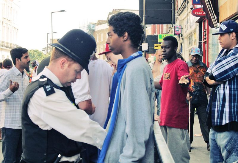 Image of the police searching a young male minority.