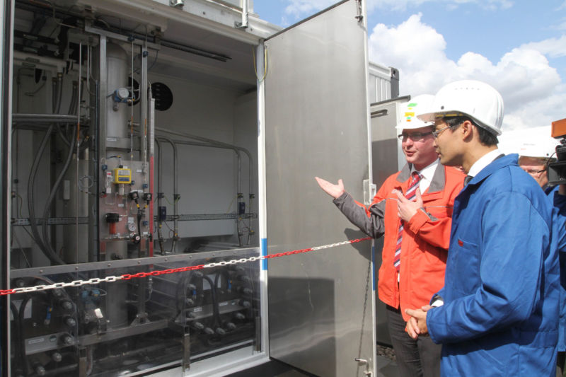 Two men looking at components in power for gas