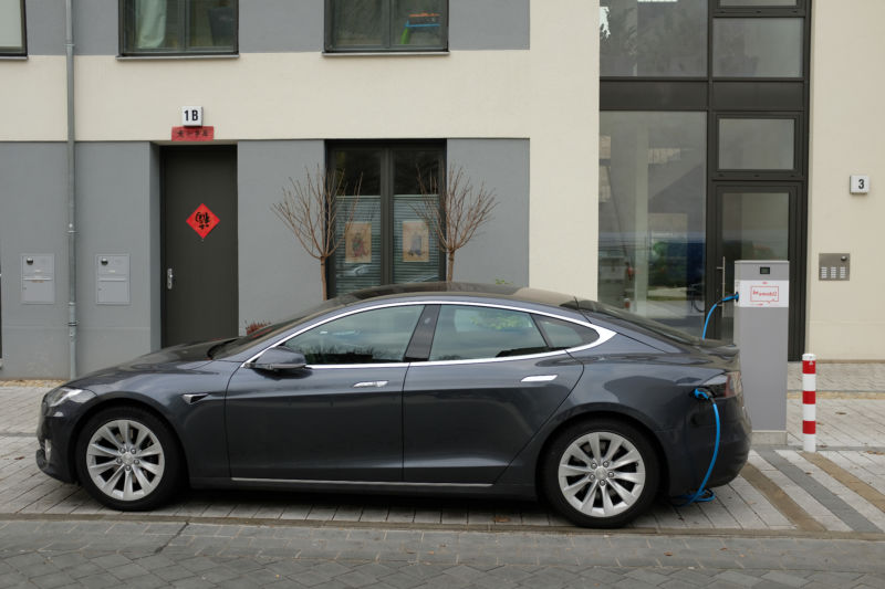 A Tesla sedan on a city street charges at a charging station.