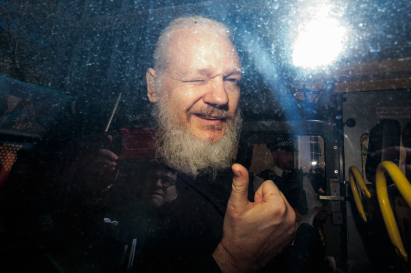Julian Assange gestures to the media from a police vehicle on his arrival at court on April 11, 2019 in London.