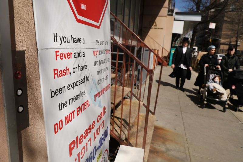 A sign warns people of measles in the ultra-Orthodox Jewish community in Williamsburg on April 10, 2019 in New York City. Mayor Bill de Blasio recently announced a state of emergency and mandated residents at the center of the outbreak to get vaccinated for the viral disease.