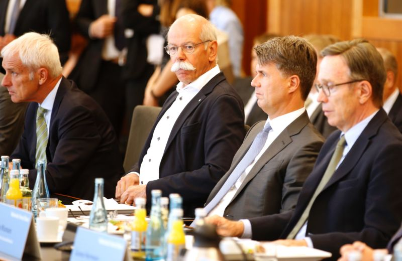 Four German auto executives sit at an event.