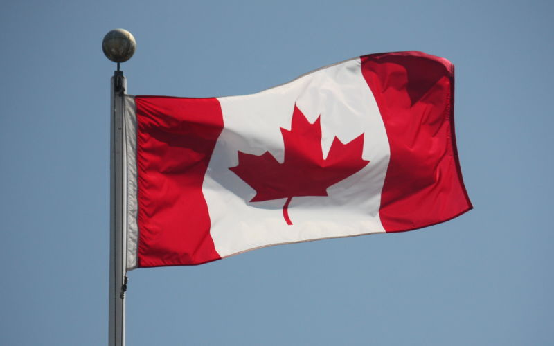The Canadian flag waves against a blue sky.