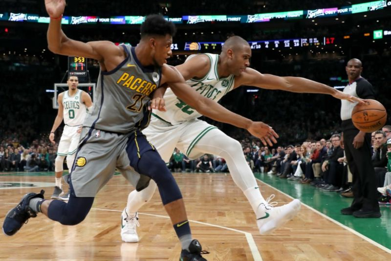 Boston Celtics' Al Horford and Indiana Pacers' Thaddeus Young chase a ball out of bounds during a March game. A new study found that a self-centered bias in time perception might affect how each perceives who touched the ball last.
