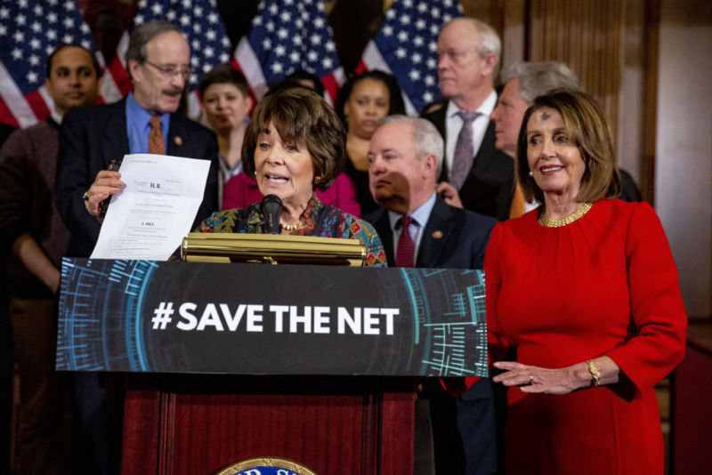 Representative Anna Eshoo (D-Calif.) Speaks as she stands behind a podium and holds a paper copy of a net neutrality bill during a press conference, while the Speaker of the House of Representatives , Nancy Pelosi (D-Calif.) And other Democrats observe.