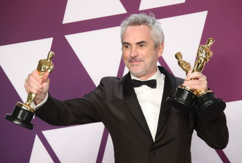 Roma director Alfonso Cuaron holding three Oscars trophies.