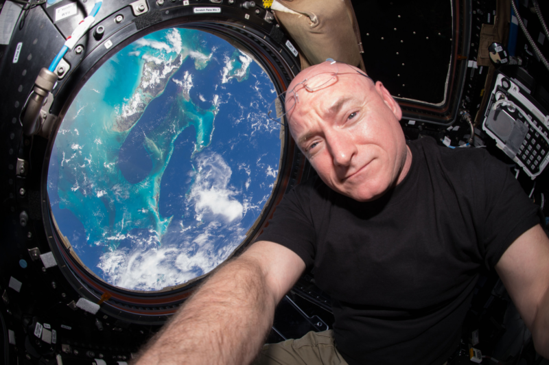 Image of an astronaut with Earth behind him in a window.