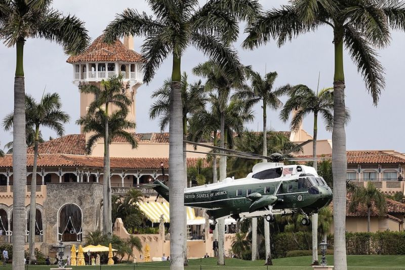 Large helicopter emblazoned with presidential logos lands at a seaside resort.