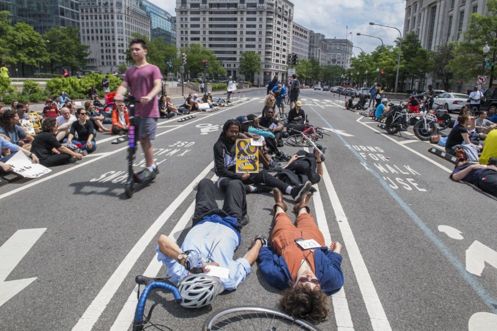 People lie on the Pennsylvania Avenue bike lane in Washington, DC, on April 26, 2019. The Rally for Streets That Don't Kill People was held outside the John A. Wilson Building to call on Mayor Muriel Bowser's administration to act on safety measures for bikers and pedestrians.