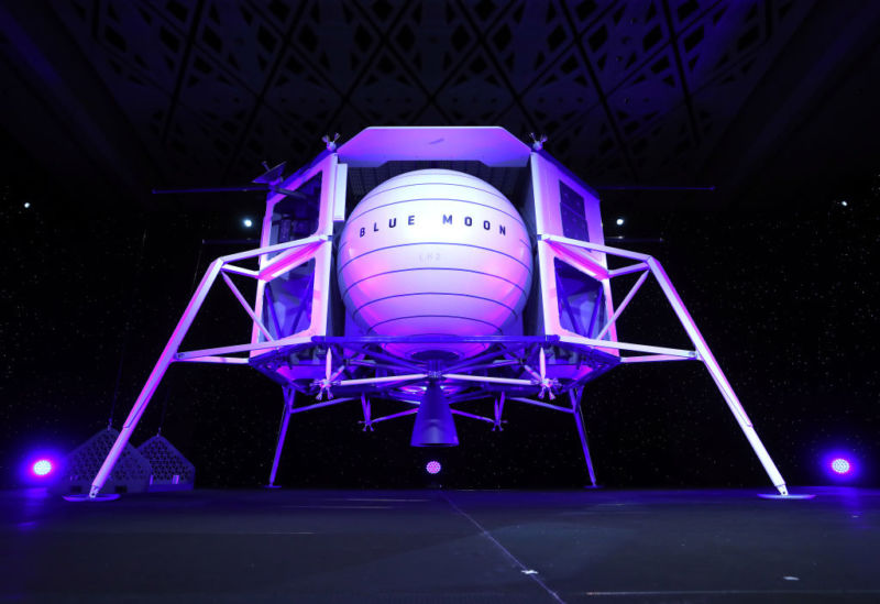 A man on stage stands in front of a full-size spacecraft model.
