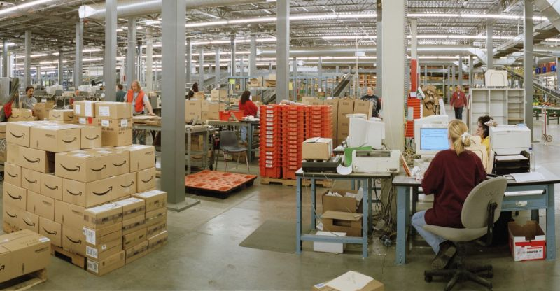 Workers and packages inside an Amazon warehouse.