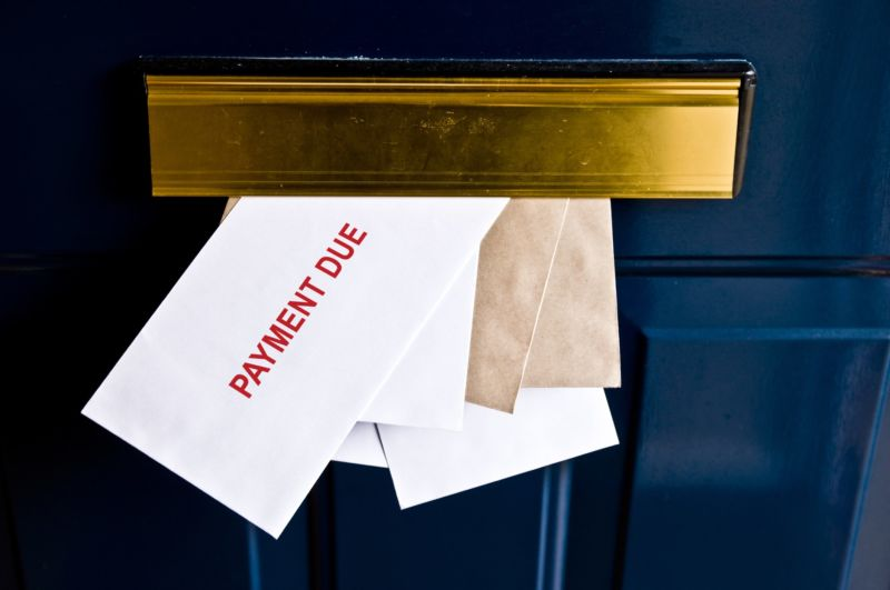 Envelopes sticking out of the mail slot in a door with the text on the top envelope saying,