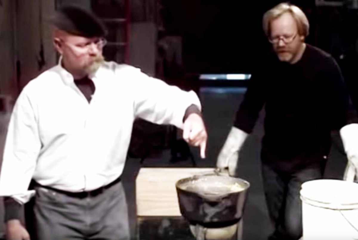 Adam Savage looks on as Jamie Hyneman dips a wetted finger into hot lead in a 2009 episode of <em>Mythbusters.</em> Thanks to the Leidenfrost effect, Jamie's finger was fine.