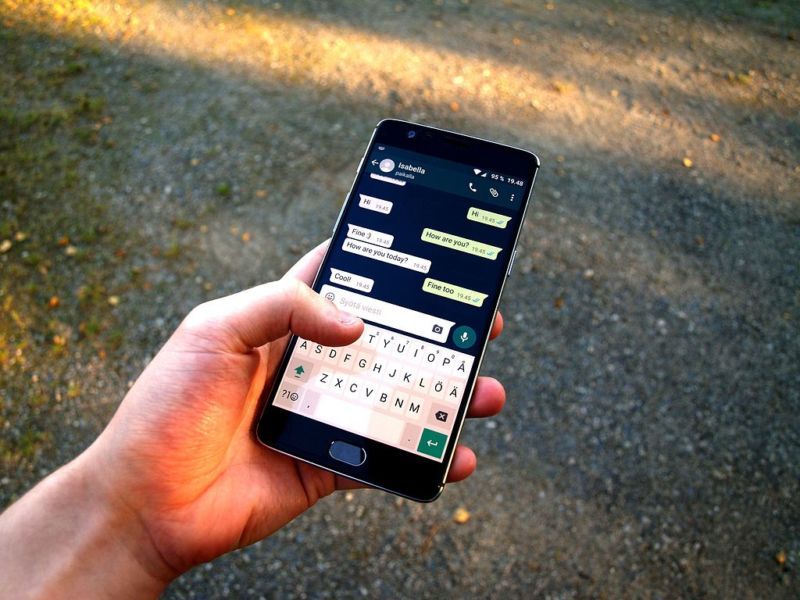 Photograph of a hand using WhatsApp on a smartphone.